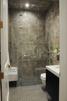 large ceiling high glass shower with marble walls