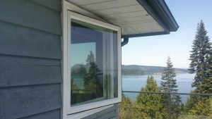 Open window with a view of a forested area and Pacific Ocean
