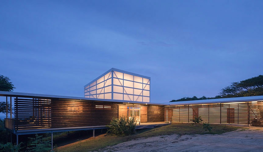 Vancouver style beach house lit up at dusk with clear sky